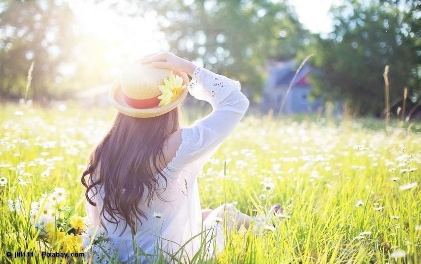 Frau sitzt in der Natur im Gras
