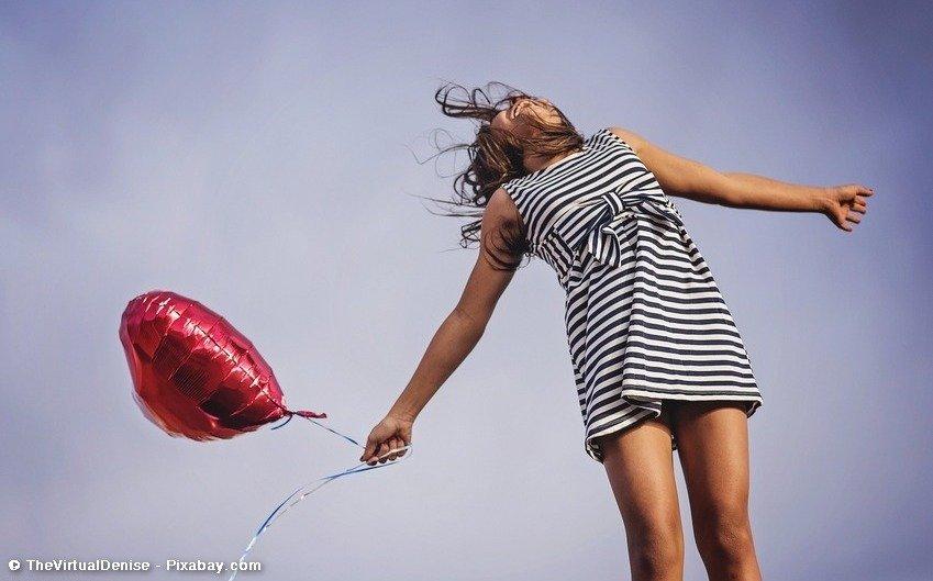 Frau macht Luftsprung, hält Luftballon in der Hand
