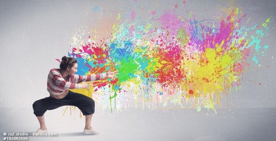 Frau tanzt vor einer Wand mit vielen Farben